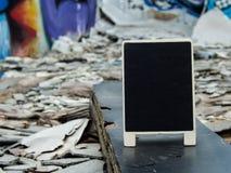 En svart tavla på det murkna övergav trät bland byggnadsröra w Royaltyfri Foto