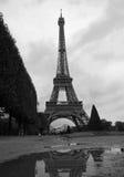 En svartvit Eiffeltorn reflekterar i en pöl under en lynnig molnig Paris himmel Arkivfoto
