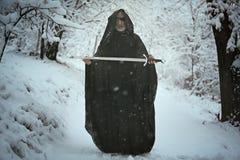 En synad gamal man som erbjuder ett svärd arkivfoton