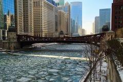 En täckt isstor bit, fryste Chicago River är aquablått och kör till och med den Chicago öglan fotografering för bildbyråer