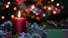 En tänd stearinljus och en gåvaask på bakgrunden av en bokeh stock video
