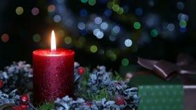 En tänd stearinljus och en gåvaask på bakgrunden av en bokeh arkivfilmer