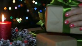 En tänd stearinljus och en gåvaask på bakgrunden av en bokeh lager videofilmer