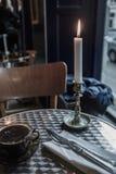 En tänd stearinljus på en äta middag tabell royaltyfri foto