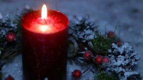 En tänd stearinljus på julnatt mot bakgrunden av konstgjord snö lager videofilmer