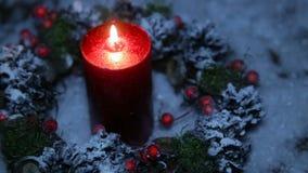 En tänd stearinljus på julnatt mot bakgrunden av konstgjord snö stock video