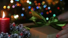 En tänd stearinljus på julnatt mot bakgrunden av konstgjord snö arkivfilmer