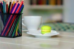 En tabell i kafét, alla i ljusa färger, vittabeller, en korg med kulöra blyertspennor på tabellen, en kopp av grönt te och ett sm arkivfoto