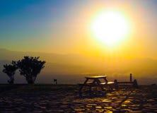En tabell med en bänk på solnedgång Royaltyfri Foto