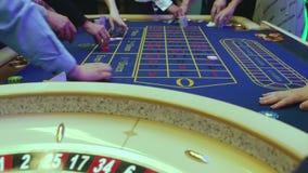 En tabell med en roulett i en kasino Croupier ger ut ett pris Spela f?r pengar Folket g?r vad p? roulett arkivfilmer