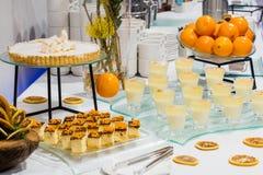 En tabell med sötsaker och frukter Arkivfoto