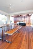 En tabell och bänkar med ett golv som göras av långa trästänger Arkivfoto