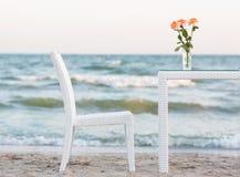 En tabell och på den en vas med rosa rosor och en bekväm stol på en härlig havsbakgrund Romantisk atmosfär på stranden Royaltyfri Fotografi