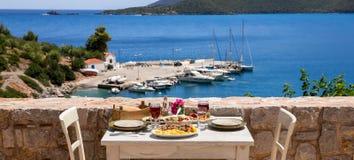 En tabell tjänade som för två med fega souvlaki- och fransmansmåfiskar, grekisk sallad, mellanmål och drinkar på sommarterrassen  Royaltyfri Foto