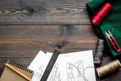 En taller de costura Materia textil, hilo, sciccors, modelo en copyspace de madera oscuro de la opinión superior del fondo Imagen de archivo libre de regalías