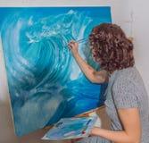 En taller pinta a la muchacha de las pinturas Fotos de archivo