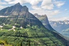 En tand formade bergprojekt som var höga ovanför dalgolvet i glaciärnationalpark royaltyfria bilder