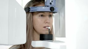 En tand- röntgenstrålebildläsare som gör en panorama- röntgenbild av käken av den unga blonda kvinnan stock video