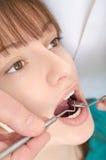 En tandläkare behandlar tänder av unga flickan arkivbilder