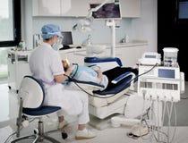 En tandläkare som arbetar i en tand- klinik royaltyfri bild