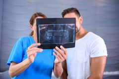 En tandläkare som förklarar resultaten av en RÖNTGENSTRÅLE till patienten Royaltyfria Bilder