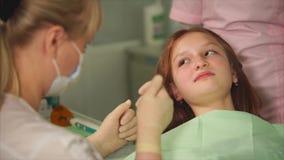 En tandläkare, som gjorde anestesi, frågar en tonårs- flicka hur hon känner sig arkivfilmer
