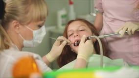 En tandläkare som gjorde en tand som borstar i en tonåring i en tand- klinik lager videofilmer