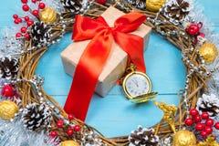 En tappningklocka i snön mot en bakgrund av en gåva och en julkrans Royaltyfria Bilder