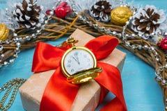 En tappningklocka i snön mot en bakgrund av en gåva och en julkrans Arkivfoto