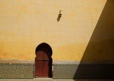 En tappninglampa på den gula väggen ovanför moroccan röda dörr- och zelligetegelplattor fungerar fotografering för bildbyråer