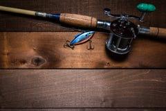 En tappningmetspö och rulle på en träplankabakgrund arkivfoton