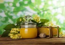 En tarro con la miel fresca de la tapa, al lado del panal y de las flores en la tabla de madera Imágenes de archivo libres de regalías