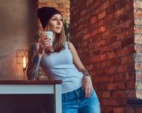 En tattoed sexig blondin i enskjorta och en hatt med koppen kaffe i ett rum med vindinre Arkivfoto