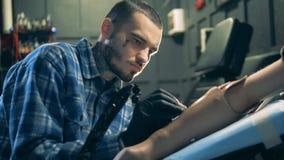En tattooer använder visarmaskinen för att dra på en handprotes, armprotes stock video