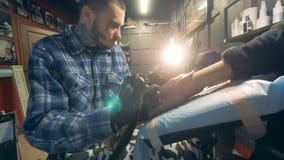 En tattooer arbetar med den rörelsehindrade mannen som drar på hans prosthetic hand stock video