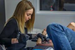 En tattooistflicka drar en tatuering på en pojkes arm i hennes smala studio royaltyfri fotografi