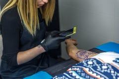 En tatueringkonstnärflicka som fotograferar tatueringen är hon, göra honom Royaltyfria Bilder