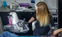 En tatueringkonstnärflicka som upp väljer färgpulver med hennes tatueringmaskin Royaltyfri Foto