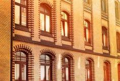 En tegelstenbyggnad med skinande fönster på solnedgången, härligt solljus reflekterade från exponeringsglaset, den gamla arkitekt fotografering för bildbyråer