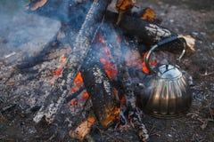 En tekanna med teställningar vid branden aftonfotografi royaltyfri fotografi