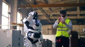 En tekniker använder VR-utrustning för att kontrollera en droid på en fabrik stock video