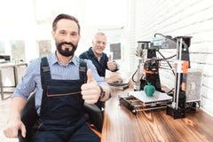 En tekniker i en funktionsduglig overall som poserar i ett tekniskt laboratorium Bak det är en skrivare 3d Arkivfoton