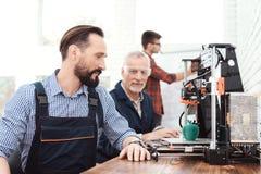 En tekniker i en funktionsduglig overall som poserar i ett tekniskt laboratorium Bak det är en skrivare 3d Royaltyfri Fotografi