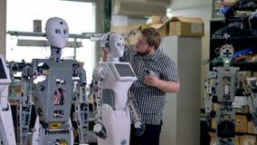 En tekniker installerar en tillbaka head räkning på en robot stock video