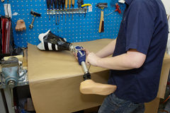 En tekniker justerar en prosthetic fot. Fotografering för Bildbyråer
