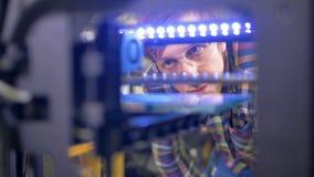 En tekniker kontrollerar arbete 3d-printer