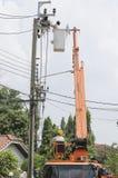 En tekniker kontrollerar hinken till höjdpunkten upp elektrikerarbete arkivbilder