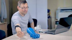 En tekniker lär kapaciteterna av en bionisk arm arkivfilmer