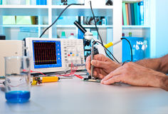 En tekniker testar elektroniska delar Royaltyfria Foton