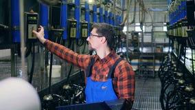 En tekniker undersöker att bruka maskiner i en ladugård, genom att använda en bärbar dator stock video